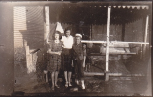 I'm standing with my mother and sister at the back porch where my father built his workshop and first TV set
